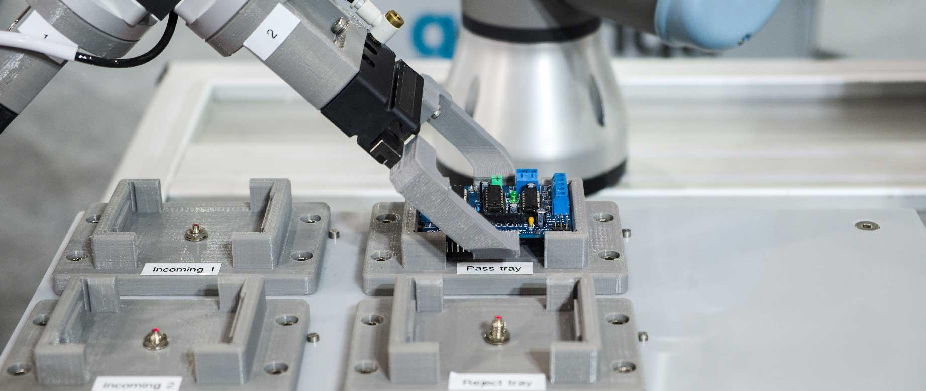 Bild eines Pick and Place Verfahrens mit Elektronikteilen. Roboterarm greift Elektronikbauteil.
