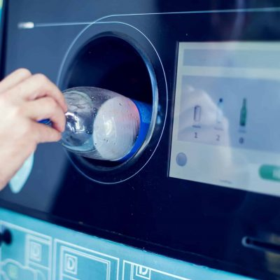 Shoppers return their bottles and cans of reusable packagings in a reverse vending machine.